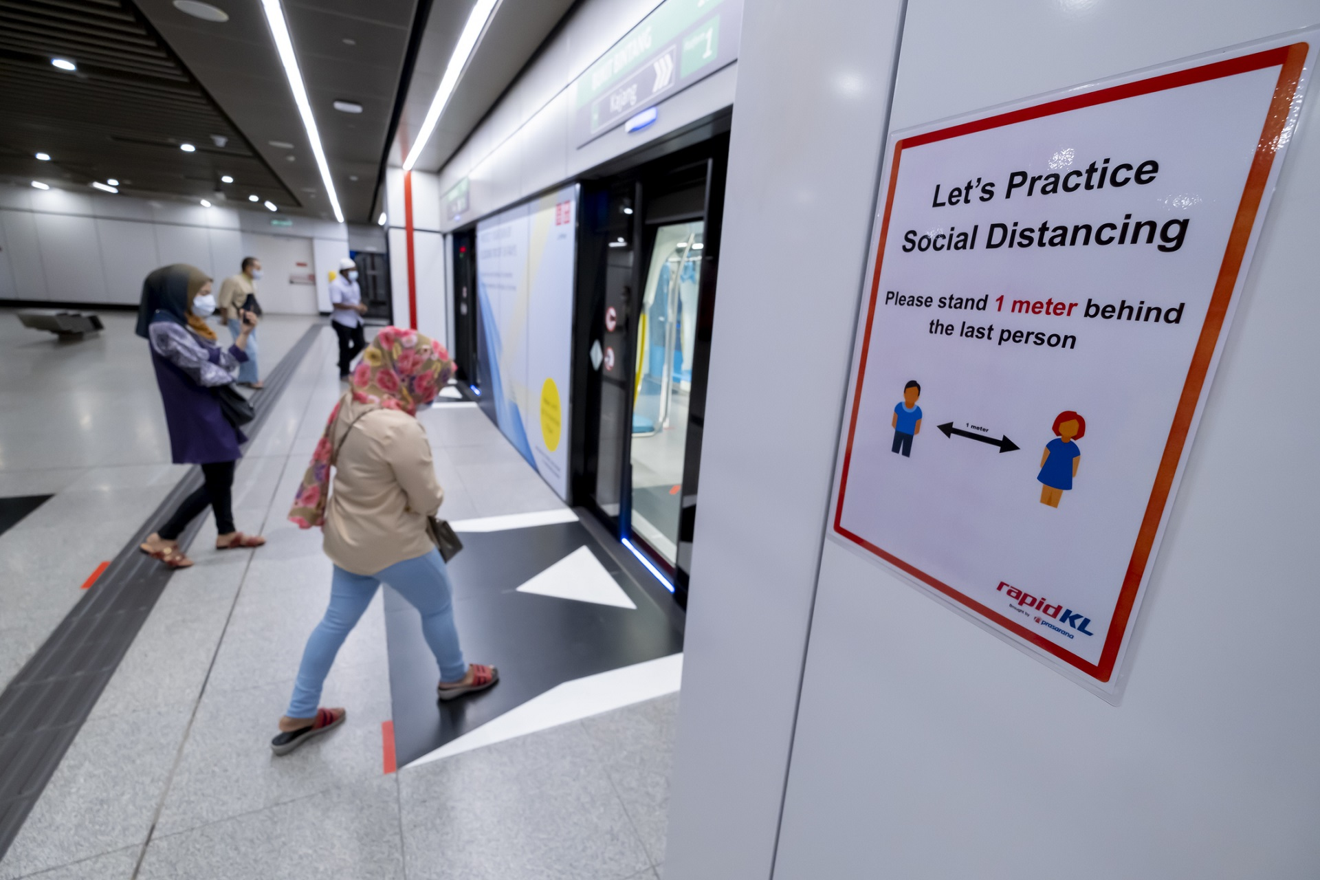 Commuters wear a face mask and practice social distancing at the MRT station in Kuala Lumpur. iStock/razaklatif